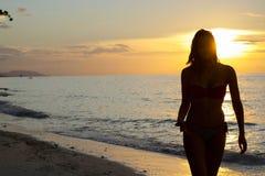 Sylwetka młodej kobiety odprowadzenie morzem przy zmierzchem Obraz Royalty Free