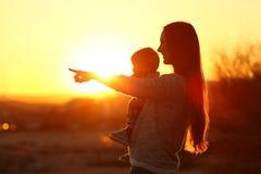 Sylwetka macierzysty wskazuje horyzont z jej dzieckiem zdjęcia royalty free