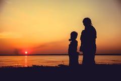 Sylwetka matka i dziecko cieszy się widok przy brzeg rzeki Fotografia Royalty Free
