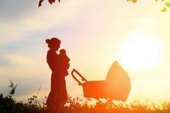 Sylwetka matka z małym dzieckiem przy zmierzchem Obrazy Royalty Free