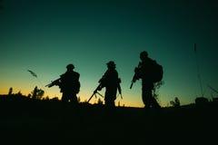 Sylwetka militarni żołnierze z broniami przy nocą strzał, hol Obrazy Stock