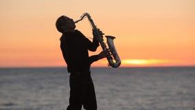 Sylwetka muzyk bawić się saksofon dalej zdjęcie wideo