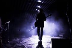 Sylwetka muzyk, piosenkarz z gitarą na scenie w promieniach reflektory fotografia stock
