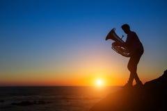 Sylwetka muzyk sztuki Tuba na dennym brzeg Fotografia Stock