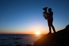 Sylwetka muzyk sztuki Tuba na dennym brzeg przy pięknym zmierzchem Zdjęcia Stock
