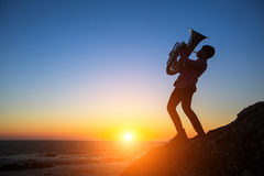 Sylwetka muzyk sztuki Tuba na dennym brzeg przy zmierzchem hobby Fotografia Stock