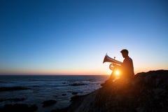 Sylwetka muzyk sztuki Tuba na dennym brzeg przy zmierzchem jazzes zdjęcie royalty free