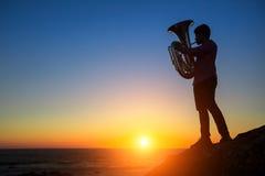 Sylwetka muzyk sztuki Tuba na morze plaży przy magicznym zmierzchem Nostalgia Obraz Stock