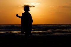 Sylwetka na plaży przy zmierzchem Zdjęcie Stock