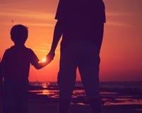 Sylwetka ojca i syna mienia ręki przy zmierzchu morzem Zdjęcia Stock