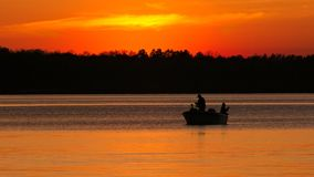Sylwetka ojca i syna połów na jeziorze przy zmierzchem obrazy stock