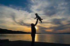 Sylwetka ojciec i jego syn przeciw zmierzchowi z dramatycznym niebem Fotografia Stock