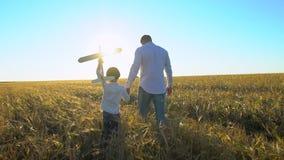 Sylwetka ojciec i syn bawić się, chodzi z samolot zabawką wpólnie przy zmierzchem w pszenicznym polu szczęśliwa rodzina na zewnąt zdjęcie wideo