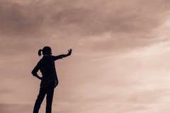 Sylwetka ono modli się nad pięknym nieba tłem kobieta Zdjęcie Stock