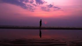 sylwetka Osamotniony Azjatycki młody człowiek chodzi pokojowo wzdłuż opustoszałej plaży przy zmierzchem seascape zbiory wideo