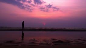 sylwetka Osamotniony Azjatycki młody człowiek chodzi pokojowo wzdłuż opustoszałej plaży przy zmierzchem seascape fotografia stock