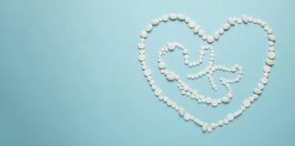 Sylwetka płodu dziecko ludzie w sercu białe pastylki na błękitnym tle Traktowanie noworodkowie, opieka medyczna obraz royalty free