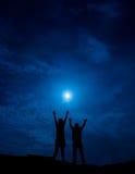 Sylwetka para przeciw księżyc w pełni z rękami up Zdjęcie Royalty Free