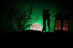 Sylwetka pary całowanie pod księżyc w pełni Faceta buziaka dziewczyny ręka na księżyc w pełni sylwetki tle Walentynki ` s dnia wy Fotografia Royalty Free