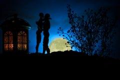 Sylwetka pary całowanie pod księżyc w pełni Faceta buziaka dziewczyny ręka na księżyc w pełni sylwetki tle Walentynki ` s dnia wy Zdjęcia Royalty Free