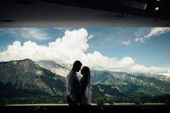 Sylwetka pary całowanie z górami Szwajcaria przez okno za one fotografia royalty free