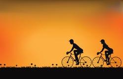Sylwetka pary jeżdżenia rower z pięknym niebem przy zmierzchem ilustracja wektor