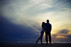 Sylwetka pary obejmowanie podczas gdy patrzejący zmierzch Zdjęcie Royalty Free