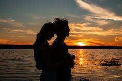 Sylwetka pary przytulenie blisko morza na zmierzchu Obrazy Royalty Free