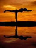 Sylwetka piękna joga kobieta z wodnym odbiciem zdjęcia royalty free
