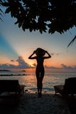 Sylwetka piękna nikła dziewczyna na zmierzchu tle i słońc loungers na oceanu brzeg Kobieta zegarka linia horyzontu Fotografia Royalty Free