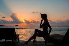Sylwetka piękna nikła dziewczyna na zmierzchu tle i słońc loungers na oceanu brzeg Kobieta zegarka linia horyzontu Zdjęcia Royalty Free