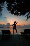 Sylwetka piękna nikła dziewczyna na zmierzchu tle i słońc loungers na oceanu brzeg Kobieta zegarka linia horyzontu Fotografia Stock