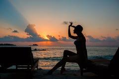 Sylwetka piękna nikła dziewczyna na zmierzchu tle i słońc loungers na oceanu brzeg Kobieta zegarka linia horyzontu Zdjęcie Stock