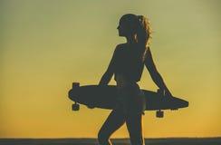 Sylwetka piękna, seksowna modniś dziewczyna stoi z longboard przeciw zmierzchowi w tatuażach, Zdjęcia Royalty Free
