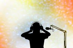 Sylwetka piosenkarza kobiety z hełmofonem i mikrofonem, pojęcie v Obraz Stock