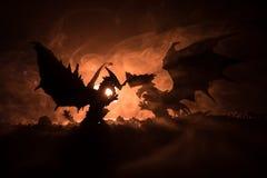 Sylwetka pożarniczy oddychanie smok z dużymi skrzydłami na zmroku - pomarańczowy tło obraz stock