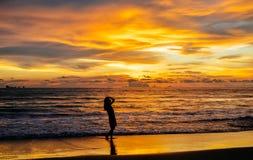 Sylwetka pojedynczy młodej kobiety odprowadzenie na plaży gdy zmierzch fotografia royalty free