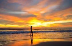 Sylwetka pojedynczy młodej kobiety odprowadzenie na plaży gdy zmierzch zdjęcia royalty free