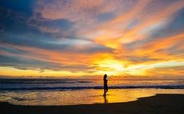 Sylwetka pojedynczy młodej kobiety odprowadzenie na plaży gdy zmierzch obrazy royalty free