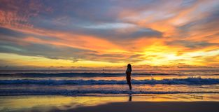 Sylwetka pojedynczy młodej kobiety odprowadzenie na plaży gdy zmierzch fotografia stock