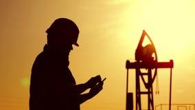 Sylwetka pole naftowe pracownik przy ropy naftowej pompą w polu naftowym przy złotym zmierzchem Przemysł, pole naftowe, ludzie i zdjęcie wideo