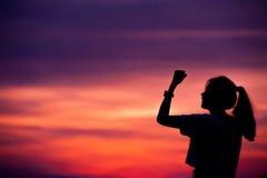 Sylwetka Pomyślna kobieta z ręką up Zdjęcia Stock