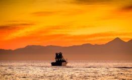 Sylwetka prędkości łódź w oceanie przy zmierzchem Obrazy Stock