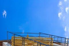 Sylwetka pracownicy budowlani na szafocie pracuje pod niebieskim niebem fotografia stock