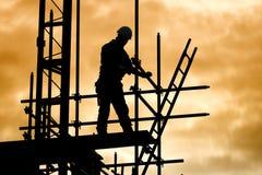 Sylwetka pracownik budowlany na rusztowanie placu budowy Zdjęcia Royalty Free