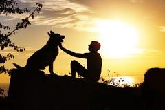 Sylwetka profil mężczyzny i psa obsiadanie przed each inny na naturze, chłopiec kares jego zwierzę domowe przy zmierzchem w polu, obrazy royalty free