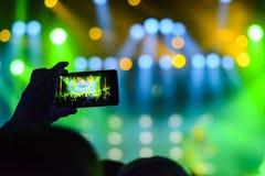 Sylwetka ręki z smartphone przy koncertem obraz stock