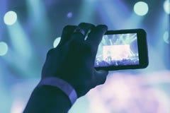 Sylwetka ręki z smartphone przy koncertem obraz royalty free