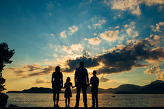 Sylwetka rodzina z dziećmi przeciw tłu położenia morze i słońce Fotografia Royalty Free