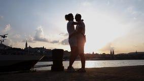 Sylwetka romantyczny pary przytulenie, całowanie na molu przy zmierzchem i zdjęcie wideo